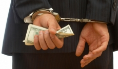Businessman with cash and handcuffs