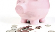 Piggy bank with coins in front of it