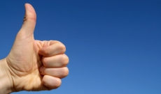 Thumbs up in front of blue sky