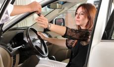 Woman receiving keys new car