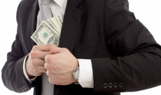 Man stuffing money into his suit
