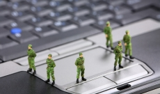 Military figurines standing on computer keyboard