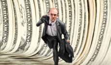 Man running through a tunnel of money
