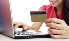 Woman with laptop holding a credit card
