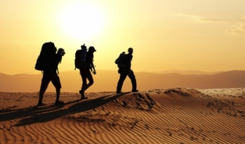 Three silhouettes of hikers in the desert