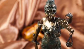 Blind Lady Justice statue with gavel in background