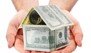 House made of money sitting on man's hands