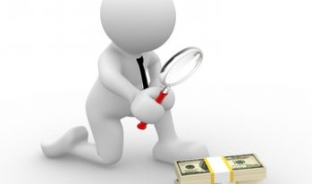 Man with magnifying glass looking at money