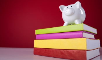 Piggy bank standing on college textbooks