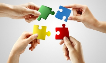 Multiple hands putting puzzle pieces together